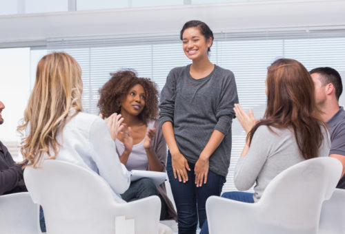 Patient has a breakthrough in group therapy and everyone is clapping her